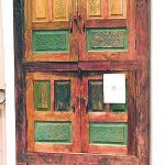 Antique cabinet doors used to make driveway gate with carved panels
