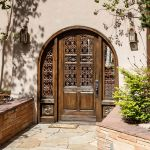 Custom arched door with antique panels and grillwork