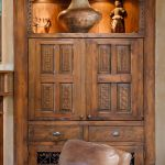 Media cabinet with carved panels and retractable doors