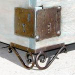 Antique key plates and iron scroll legs on queen bed