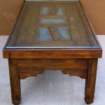 coffee table with carved panels and blue patina