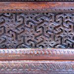 Detail of antique carved panel in finished buffet cabinet