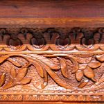 Detail of carving on antique fireplace mantel and surround