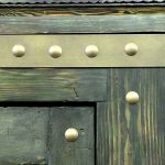 Detail of bronze strapping and clavos on custom front entry
