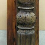 An antique carved column accents a custom kitchen island