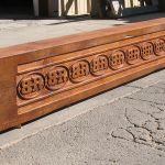Salvaged heavy timber beam carved with guest ranch brand
