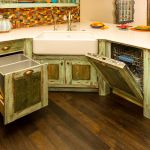 Green kitchen cabinets featuring wood paneled dishwasher and recycling drawer