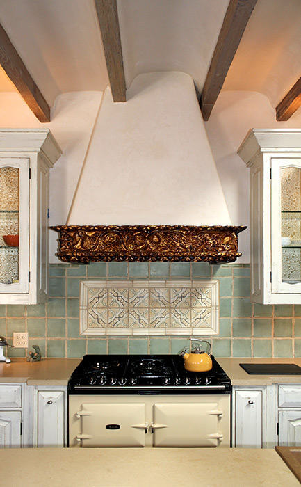 gold leaf stove hood in remodeled kitchen