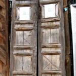antique doors used to make bedroom entry with peaked surround